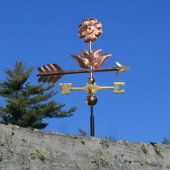 small flower weathervane with blue sky background