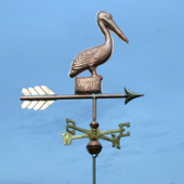 Small Pelican Weathervane standing on a Post, right angle view with a dark blue sky background.