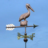Pelican Weathervane standing on a Post, right side view with a dark blue sky background.