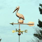 Small Pelican Weathervane standing on a Post, left side view with a light green sky background.