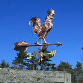 Large Walking Rooster Weathervane slight right front view on dark blue sky background.