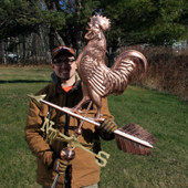 Nate holding our new large walking rooster weathervane with green grass and trees background.