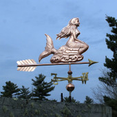 Large Mermaid Weathervane right side view on dark blue sky background.