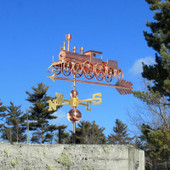 Copper Train Wind Vane with spoke wheels on an arrow, front left side view on blue sky background.