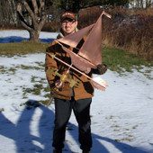 Nate holding Yacht Weathervane on grass and snow background.