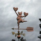 Pig with hearts weathervane, left side view on stormy sky background.