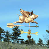 Flying Pig Wind Vane with Arrow right side view on blue sky background.