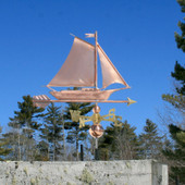 Friendship Sloop/Sailboat Weathervane right angle view on blue sky background.