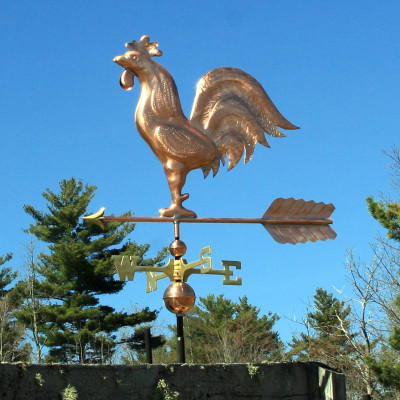 Copper Rooster weathervane left side view on blue sky background