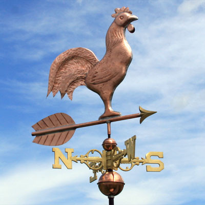 rooster weathervane right front view on blue and cloudy sky background