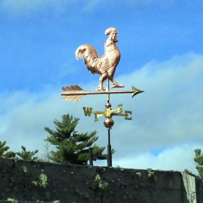 small rooster weathervane side view on blue sky image