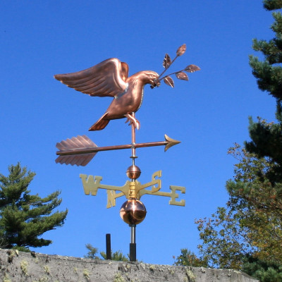 dove weathervane carrying an olive branch right front angle view on blue sky background