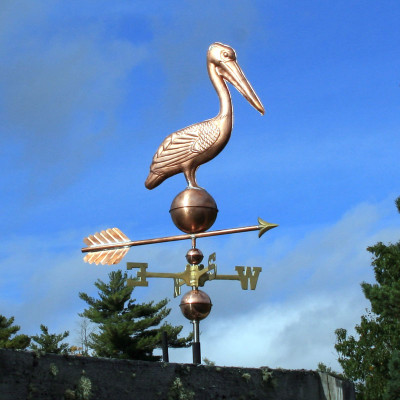Pelican on Ball Weathervane right side view on blue sky background