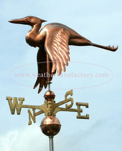 flying heron weathervane left side view on blue sky background