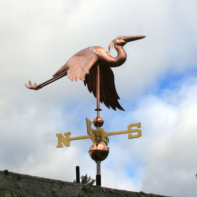 flying heron weathervane with the wings down right front view on cloudy and blue sky background