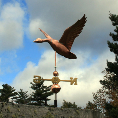 Flying Goose Weathervane left side view on blue and cloudy sky background