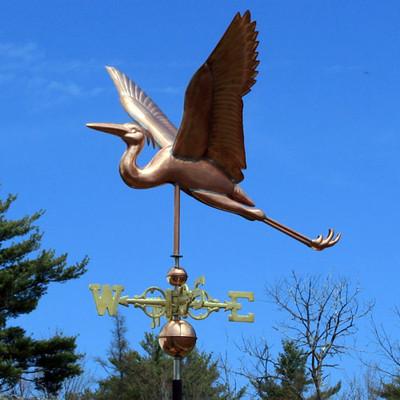 blue flying heron weathervane left side view on blue sky background