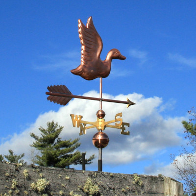 Flying Duck Weathervane right side view on blue and cloudy sky background