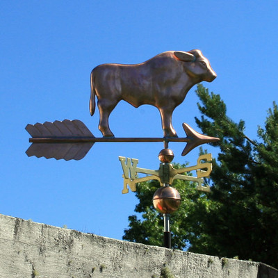 bull weathervane right side view on blue sky background