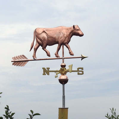 Cow Weathervane right side view on gray sky background