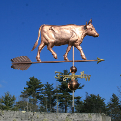 large cow with horns weathervane right side view with blue sky background