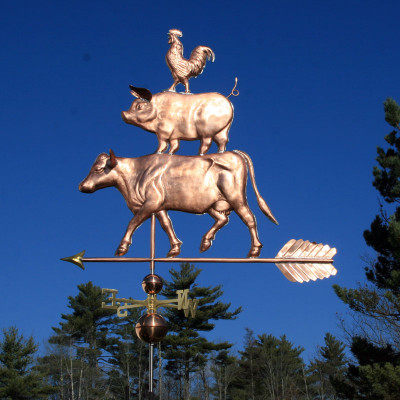 Large Barnyard Weathervane of rooster standing on a pig, with the pig standing on large cow left side view on blue sky background.