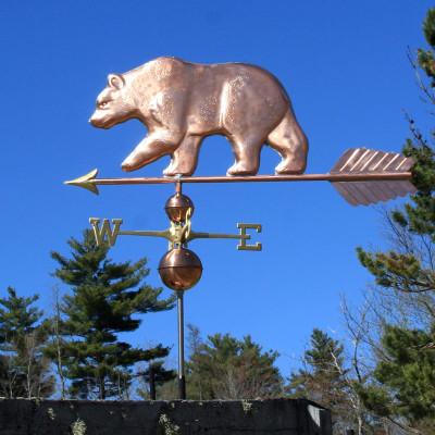 large bear weathervane left side view on blue sky background