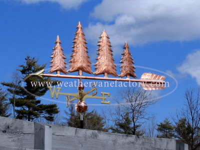 Large Four Trees Weathervane left side view on a blue sky background.