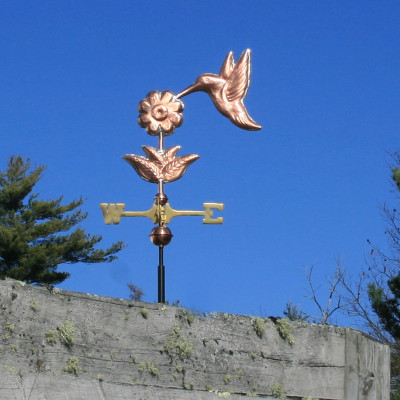 hummingbird weathervane side view on blue sky background