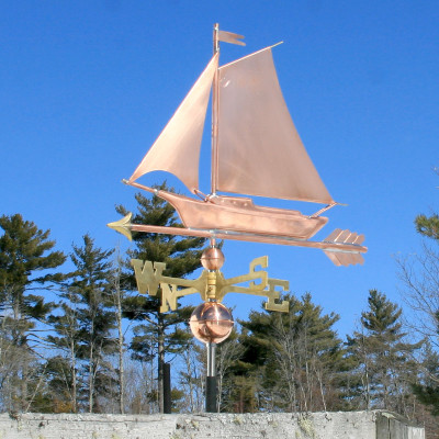 Friendship Sloop/Sailboat Weathervane left angle view on blue sky background.