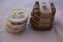 Baby cakes raw puer On the left are the individual cakes that weigh 8g each. On the right is a bundle of seven of the 8g baby cakes wrapped in bamboo.