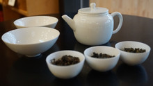 2 wide cups, teapot, and three oolong samples with brew instructions and tasting notes