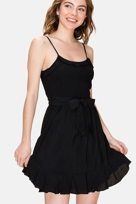 Black fit and flare dress with smocked bodice and ruffle trim.