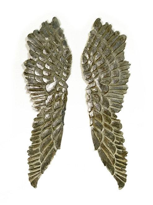 """Pair Of Carved Angel Wings Wall Decor Pair Of Carved MDF Wood Angel Wings Wall Decor.  Silver Foil Paper Details, antiqued white-washed finish.  Wings can be hung from either direction with saw-tooth hangers on top and bottom of backside.  Can be hung in a """"V"""" as a Symbol of Victory.  This is an extremely fast selling item!  These are made from MDF which carves especially well using CNC as well as chip carving by hand.  MDF also offers the advantage of retaining its shape as well as preventing cracks that occur in solid wood products.  The smooth texture on the wings allow for excellent hand finishing with silver foil paper and antiquing.   Made in India"""