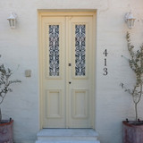 Yellow door, white brick house with vertical house numbers in bronze. A classic serif font.