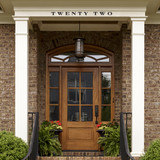 Traditional serif letters that are wide and thick above a traditional doorway with two ferns and a wood door with a hanging lantern centered in the entry