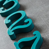 Teal blue house numbers that have curled ends and resemble a typewriters letters