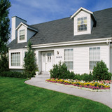 A white house with flower beds and farmhouse black house numbers