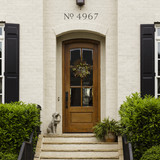 A traditional white brick house with black shutters and arched doorway with stone steps. Numbers above the doorway in a traditional serif font that reads No. 4967 in black