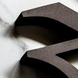 A sharp classic serif font in bronze cast aluminum number three.