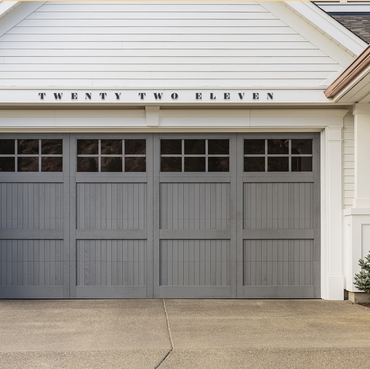 surveyor black serif font with a high contrast in thicks and thins written out house numbers above a grey farmhouse garage door on a white farmhouse with copper gutters
