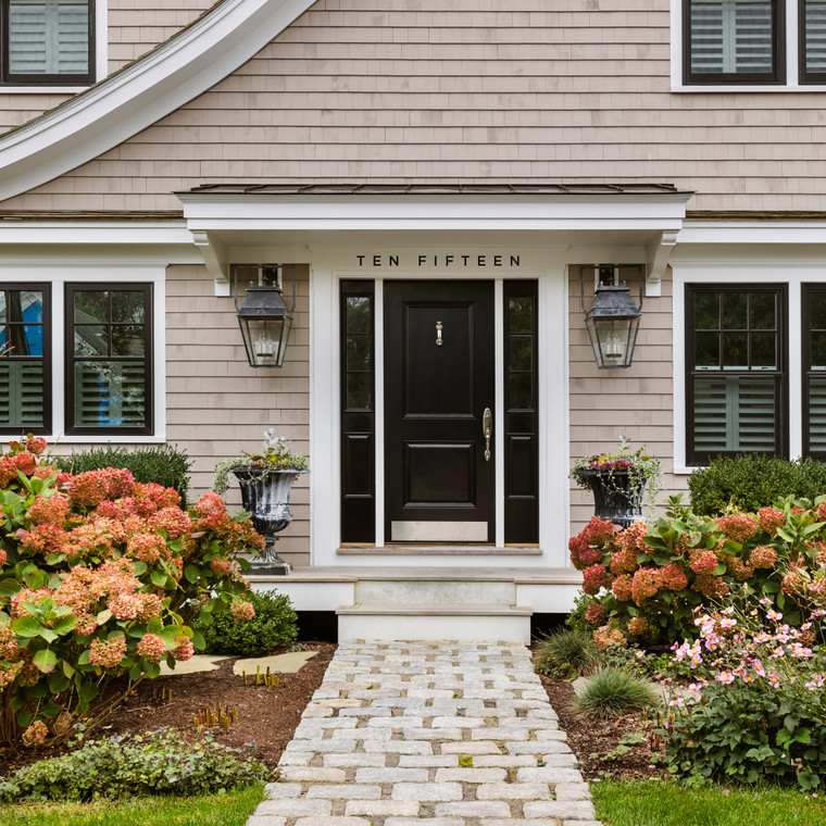 San serif Gotham Medium modern house numbers in black over a black door with white trim. a tan shingle shake house with black windows and white trim. Pebble walkway and hydrangeas