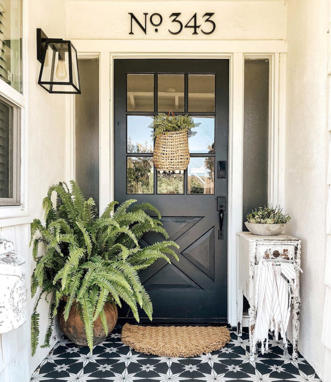 A white house with black door and patterned tile. House numbers above door in a traditional serif reading No. 343