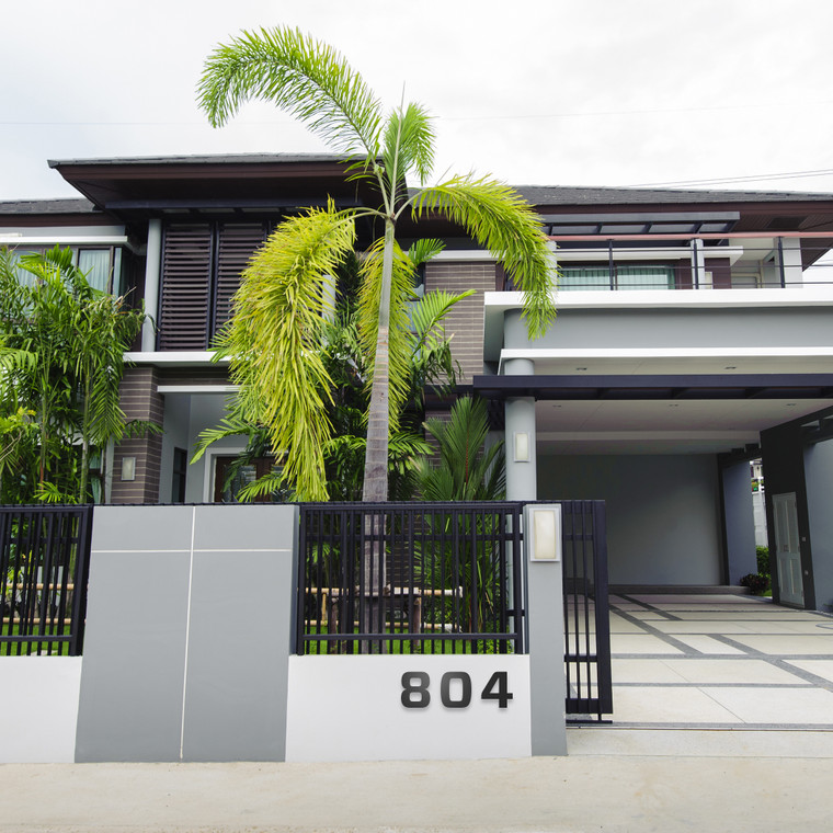 Modern house in grey and white stucco with horizontal wood siding. A large palm tree and modern front gate with bold modern house numbers on pony wall.