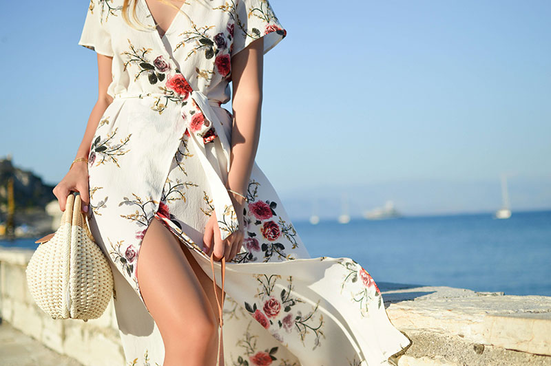 woman with a floral dress walking with a bag on a beach