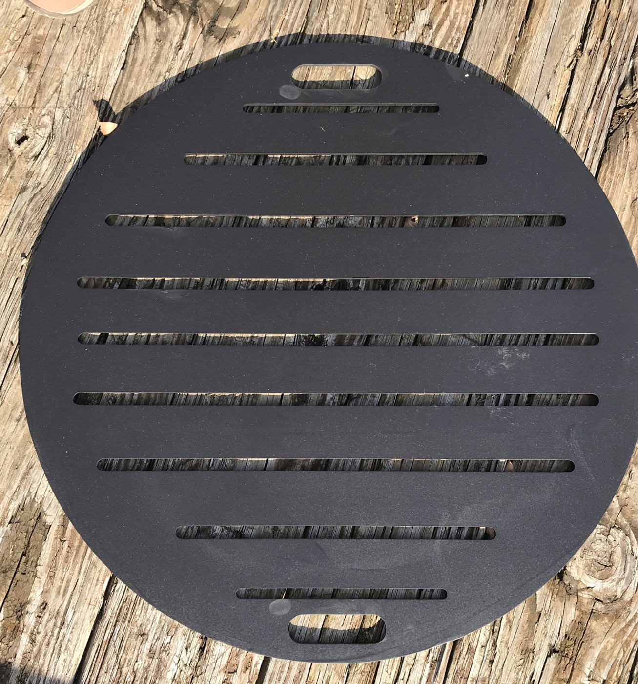 """Fire pit grate created using 1/4"""" mild carbon steel painted black with two handles.  Not for cooking"""
