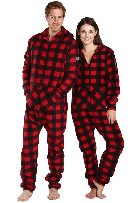two adults are wearing matching red and black plaid onesie pajamas