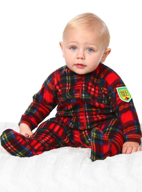 a small baby with just a bit of blonde hair is sitting up, wearing a red tartan footie pajama