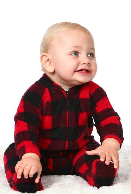 an infant with peach skin and a dusting of blonde hair is sitting up, wearing a red and black plaid footie pajama