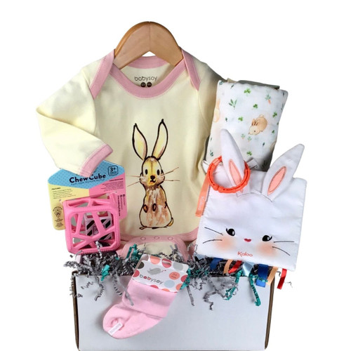 an assembly of baby gifts: a bodysuit with a bunny print, socks, a cloth book, a silicone teether, a swaddle